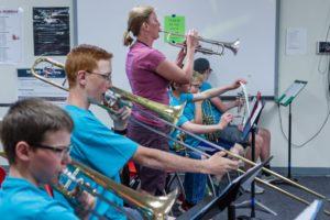MAT Camp class learning to play the trombone