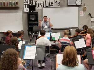 Mat Camp faculty member teaching string instruments