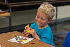 A young boy enjoying a craft project at MAT Camp