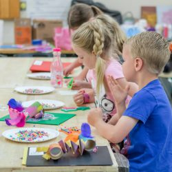 Young MAT Campers learning a new craft